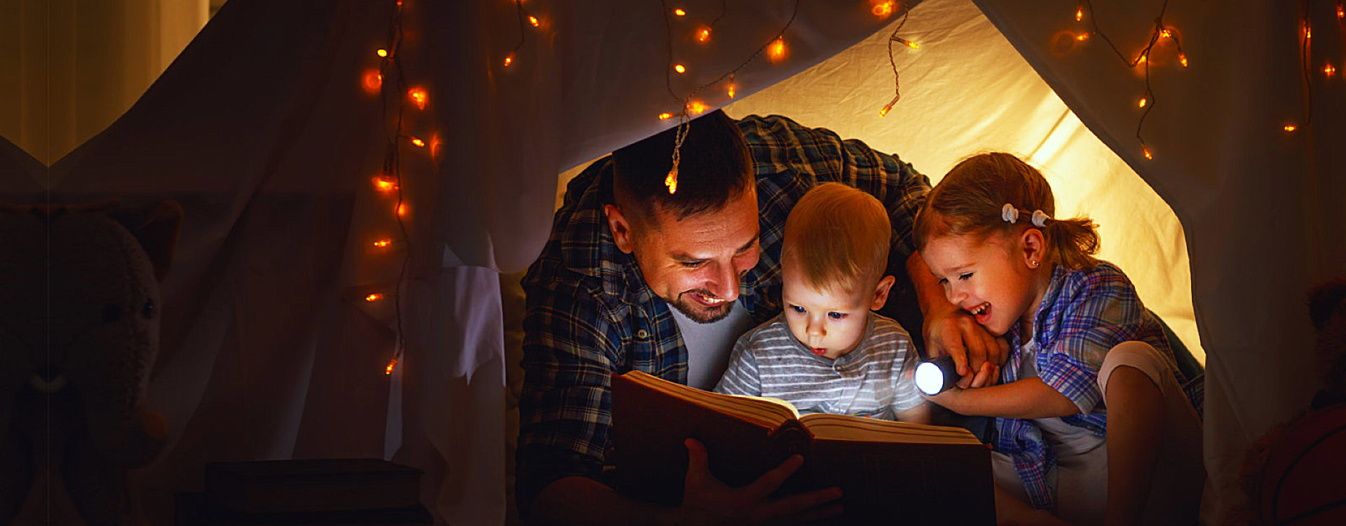 man and two children reading book